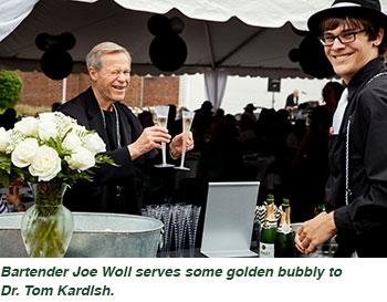 Bartender Joe Woll serves some golden bubbly to Dr. Tom Kardish.