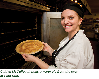 Caitlyn McCullough pulls a warm pie from the oven at Pine Run.