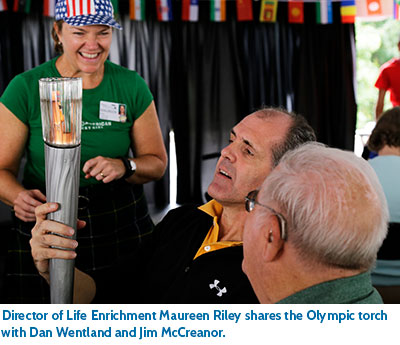 Director of Life Enrichment Maureen Riley shares the Olympic torch with Dan Wentland and Jim McCreanor.