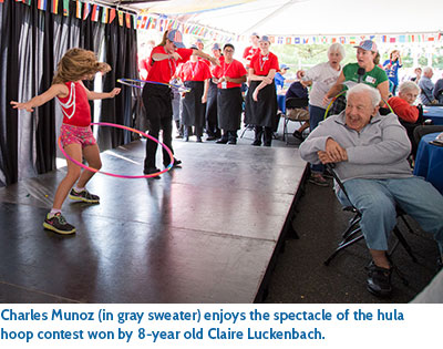 Charles Munoz (in gray sweater) enjoys the spectacle of the hula hoop contest won by 8-year old Claire Luckenbach.