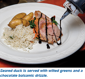 Seared duck is served with wilted greens and a chocolate balsamic drizzle.