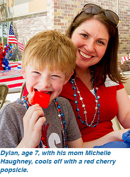 Dylan, age 7, with his mom Michelle Haughney, cools off with a red cherry popsicle.