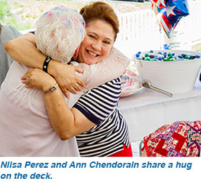 Nilsa Perez and Ann Chendorain share a hug on the deck.