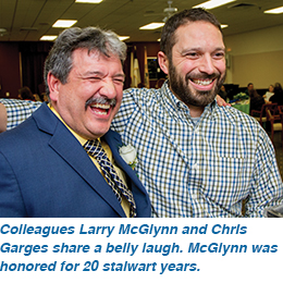 Colleagues Larry McGlynn and Chris Garges share a belly laugh. McGlynn was honored for 20 stalwart years.
