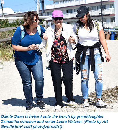 Odette Swan is helped onto the beach by granddaughter Samantha Jonsson and nurse Laura Watson.
