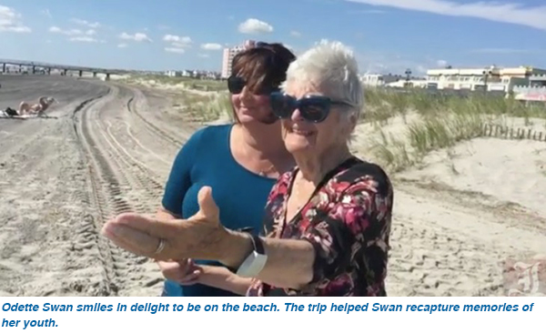Odette Swan smiles in delight to be on the beach. The trip helped Swan recapture memories of her youth.