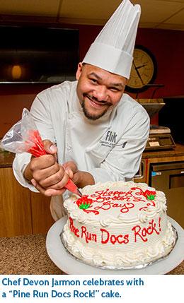 "Chef Devon Jarmon celebrates with a ""Pine Run Docs Rock!"" cake."