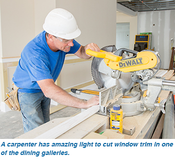 A carpenter has amazing light to cut window trim in one of the dining galleries.