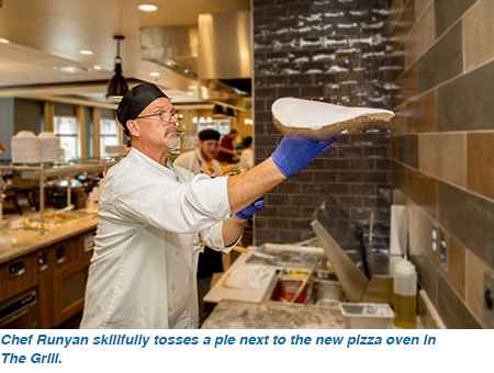 Chef Runyan skillfully tosses a pie next to the new pizza oven in The Grill.