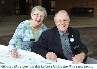 Villagers Mary Lee and Bill Leiser signing the final steel beam.
