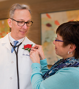 Vicki Bosler pins a carnation on Dr. Martynek