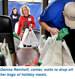 Denise Reinhoff, center, waits to drop off her bags of holiday meals.