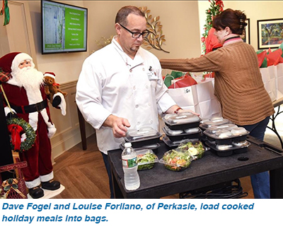 Dave Fogel and Louise Forliano, of Perkasie, load cooked holiday meals into bags.