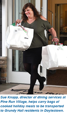 Sue Knapp, director of dining services at Pine Run Village, helps carry bags of cooked holiday meals to be transported to Grundy Hall residents in Doylestown.