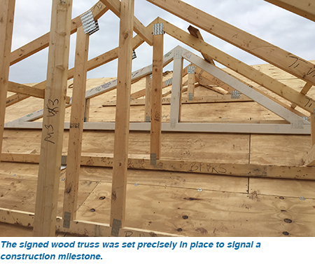 The signed wood truss was set precisely in place to signal a construction milestone.