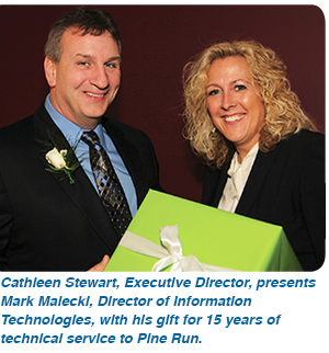 Cathleen Stewart, Executive Director, presents Mark Malecki, Director of Information Technologies, with his gift for 15 years of technical service to Pine Run.